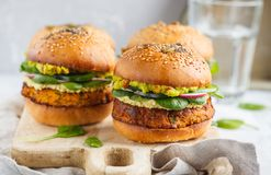 Healthy baked sweet potato burger with whole grain bun, guacamole, vegan mayonnaise and vegetables on a wooden board. Vegetarian