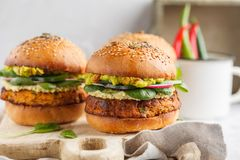 Healthy baked sweet potato burger with whole grain bun, guacamol. E, vegan mayonnaise and vegetables on a board. Vegetarian food concept, light background royalty free stock photos