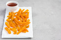 Healthy baked sweet potato fries on white plate served with spicy sauce Royalty Free Stock Photo
