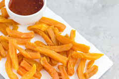 Healthy baked sweet potato fries on white a plate served with spicy sauce, copy space Stock Photo