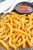 Healthy baked sweet potato fries on a wooden board served with spicy sauce, vertical Royalty Free Stock Photos