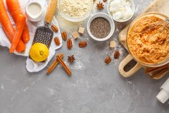 Healthy baking of carrot cake, vegan dessert ingredients: dough. In a bowl, chia, coconut butter, almond milk, nuts. Carrot bread, gray background stock photography