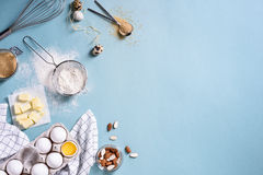 Healthy baking ingredients - flour, almond nuts, butter, eggs, biscuits over a blue table background. Bakery background frame. Top. View, copy space stock photos