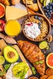Healthy balanced breakfast on a dark background. Muesli, milk, juice, croissants, cheese, biscuits stock photo