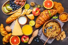 Healthy balanced breakfast on a dark background. Muesli, milk, juice, croissants, cheese, biscuits. And fruit, top view stock photo