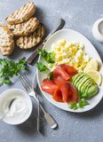 Healthy balanced breakfast or snack - smoked salmon, egg salad and avocado. On a gray background, top view. Healthy food. Concept Royalty Free Stock Photos