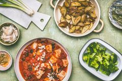Healthy balanced eating concept. Pan with chicken pieces in tomatoes sauce, green cooked broccoli and baked potatoes royalty free stock photo