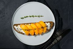 Healthy balanced food sandwich with persimmon and soft cheese on black background. stock image