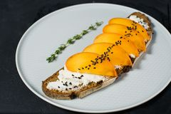 Healthy balanced food sandwich with persimmon and soft cheese on black background. royalty free stock image