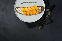 Healthy balanced food sandwich with persimmon and soft cheese on black background. royalty free stock photos