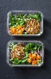 Healthy balanced lunch box. Grilled chicken zucchini burgers with broccoli, pumpkin, green pea salad on a dark background, top vie Royalty Free Stock Image
