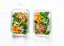 Healthy balanced lunch box. Grilled chicken zucchini burgers with broccoli, pumpkin, green pea salad on a light background, top vi Royalty Free Stock Image