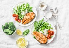 Healthy balanced mediterranean diet lunch - baked salmon, rice, green peas and green beans on a light background, top view. Flat lay Stock Photography