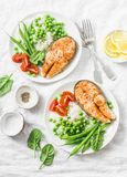 Healthy balanced mediterranean diet lunch - baked salmon, rice, green peas and green beans on a light background, top view.