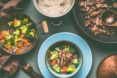 Healthy balanced nutrition dish in pots and bowls with beef meat, steamed vegetables and rice on table background with plate and c stock images