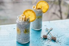 Healthy banana milk pudding with chia and orange in glass jar close up decorated with two vintage spoons with raw chia seeds Stock Image