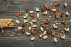 Healthy bar with nuts and seeds on the wooden background, top view Royalty Free Stock Photos