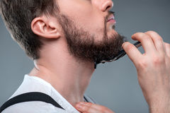 Healthy bearded young guy with sharp razor Stock Image
