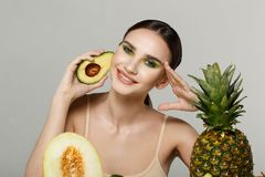 Healthy beautiful brunette girl smiling, looking at the camera with avocado in hand near face stock images