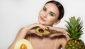 Healthy beautiful brunette girl smiling, looking at the camera with avocado in hand near face, posing in the studio on royalty free stock image