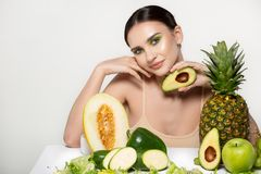Healthy beautiful brunette girl smiling, looking at the camera with avocado in hand near face, posing in the studio on stock image