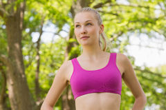 Healthy and beautiful woman in sports bra against trees in park Royalty Free Stock Image