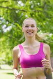Healthy and beautiful woman in sports bra jogging in park Stock Photography
