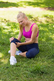Healthy and beautiful woman in sportswear sitting in park Royalty Free Stock Photos