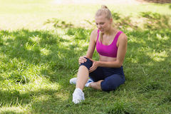 Healthy and beautiful woman in sportswear sitting in park Royalty Free Stock Photo