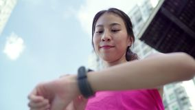 Healthy beautiful young Asian Athlete woman setting and checking progress looking heart rate monitor on smart watch while run.