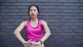 Healthy beautiful young Asian Athlete women in sports clothing legs warming and stretching her arms to ready for run. Healthy beautiful young Asian Athlete stock video