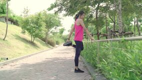 Healthy beautiful young Asian Athlete women in sports clothing legs warming and stretching her arms to ready for run. Healthy beautiful young Asian Athlete stock footage