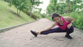 Healthy beautiful young Asian Athlete women in sports clothing legs warming and stretching her arms to ready for run. Healthy beautiful young Asian Athlete stock video footage