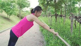 Healthy beautiful young Asian Athlete women in sports clothing legs warming and stretching her arms to ready for running on street. In urban city park stock video footage