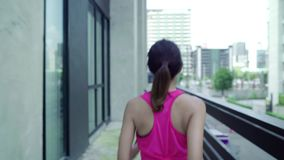 Healthy beautiful young Asian runner woman in sports clothing running and jogging on street in urban city. Lifestyle fit and active women exercise in the city stock footage