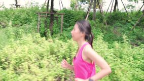 Healthy beautiful young Asian runner woman in sports clothing running and jogging on street in urban city park. stock footage
