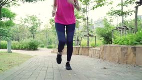 Healthy beautiful young Asian runner woman in sports clothing running and jogging on street in urban city park. Lifestyle fit and active women exercise in the stock video