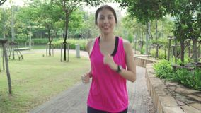 Healthy beautiful young Asian runner woman in sports clothing running and jogging on street in urban city park. Lifestyle fit and active women exercise in the stock footage