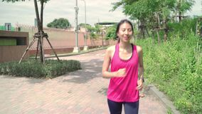Healthy beautiful young Asian runner woman in sports clothing running and jogging on street in urban city park. Lifestyle fit and active women exercise in the stock video footage