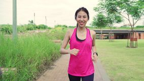 Healthy beautiful young Asian runner woman in sports clothing running and jogging on street in urban city park. stock video footage
