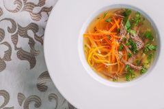 Healthy beef broth with vegetables and meet served on white plate, product photography for restaurant and gastronomy stock photography