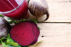 Healthy beet juice and raw beetroot on wooden table Royalty Free Stock Images