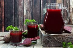 Healthy beet juice, scene on rustic dark wood Royalty Free Stock Images