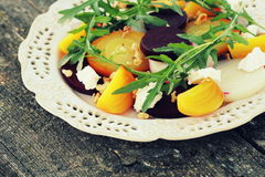 Healthy Beet Salad with red, white, golden beets, arugula, nuts, feta cheese on wooden background Stock Photos