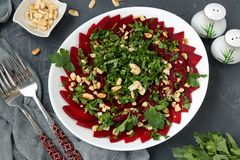 Healthy beetroot salad with peanuts and parsley on a white plate royalty free stock photo