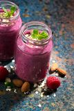 Healthy berry smoothie in a bottle on a dark background, closeup. Healthy berry smoothie in a bottle on a dark background, vertical Stock Image