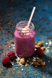 Healthy berry smoothies with oatmeal in bottle. On a dark background, closeup, vertical Royalty Free Stock Image