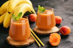 Healthy beverage - banana and apricot smoothie.  stock photography