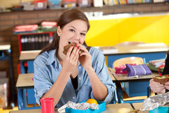 Healthy bite. Schoolgirl sitting in the classroom having a healthy sandwich Royalty Free Stock Images