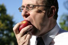 A Healthy bite. Businessman wearing business clothes about to take a bite into a rosy red apple, showing face, hand, apple and blue sky behind him stock photos